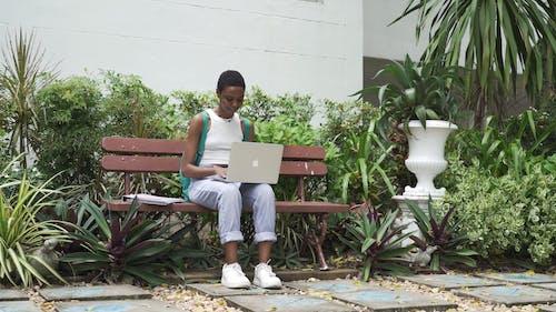 Kobieta Siedząca Na ławce Podczas Korzystania Z Laptopa, A Następnie Wita Się Z Przyjaciółką