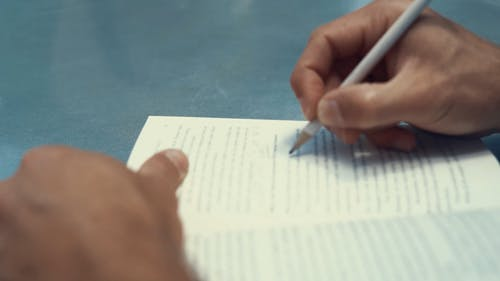 Close-Up View of Person's Hands Writing on a Book