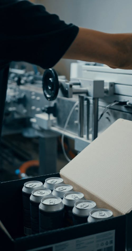 A Person Boxing Newly Canned Beers