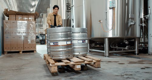 A Man Pushing a Trolley With Kegs Inside a Factory