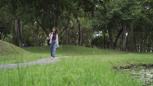 A Woman Walking in a Park While Holding Her Smartphone