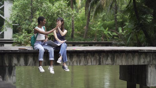 Two Women Sitting on Wooden Planks While Doing High Five