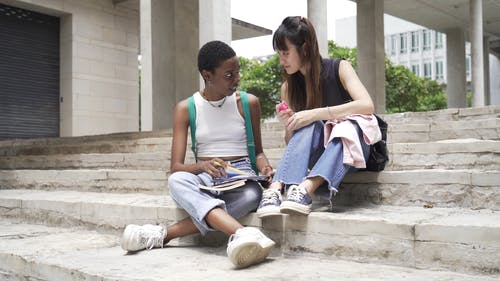 Two Women Sitting on Concrete Stairs While Reviewing Their Notes