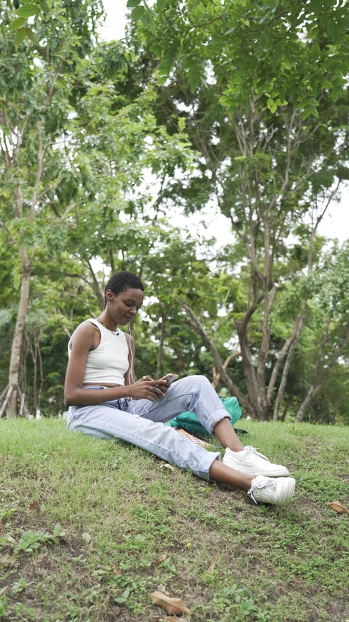A Woman Sitting on Grass While Using Her Smartphone