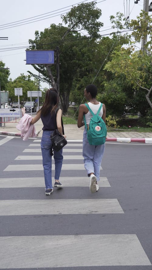 Two Women Crossing the Street While Talking to Each Other