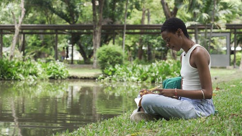 A Woman Sitting on Grass by the Pond While Studying Her Notes