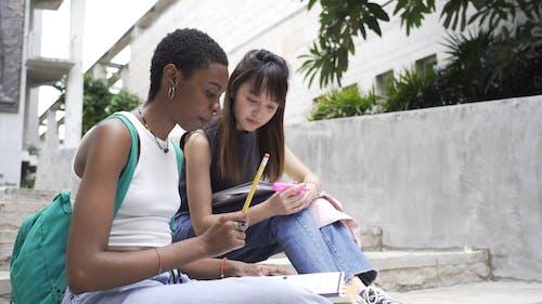 妇女在户外审查他们的学校作业