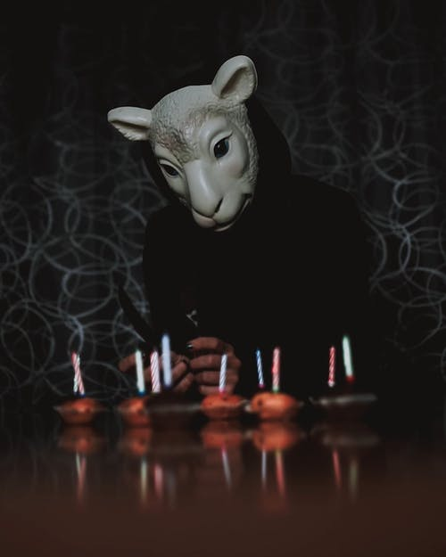 A Person Wearing a Mask Playing with Candles on Cupcakes