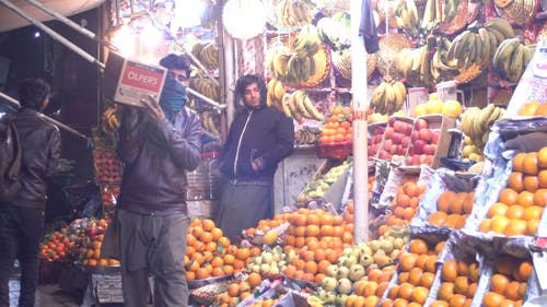 Man Standing in Front of a Fruit Stand