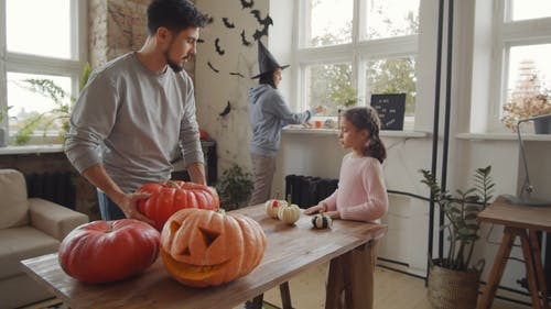 A Family Decorating Their Home In Time For Halloween