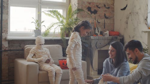 Parents Wrapping Their Kids Into A Mummy