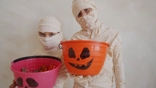 Kids In Mummy Costume Holding A Trick Or Treat Bucket