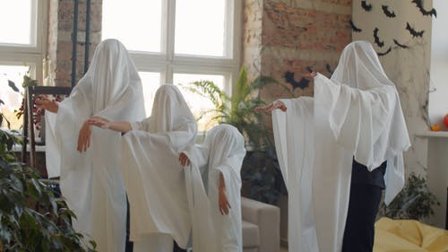 A Family Acting As Ghosts For The Halloween