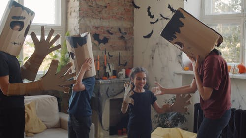 A Family Wearing Handmade Halloween Masks At Home