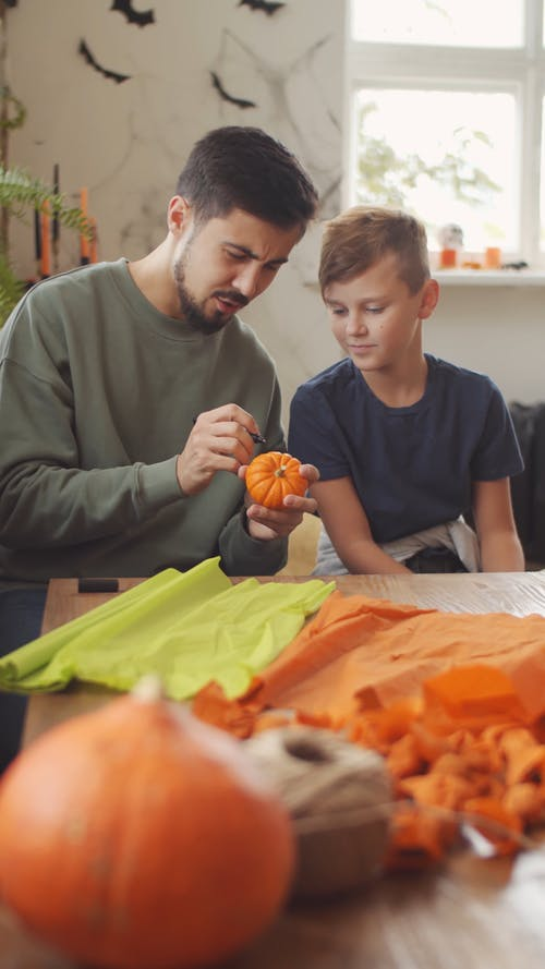 A Father Showing His Son How To Make Halloween Decors