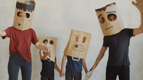 A Family Wearing Paper Bag Masks For Halloween