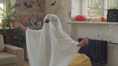 A Kid Wearing A Ghost Costume