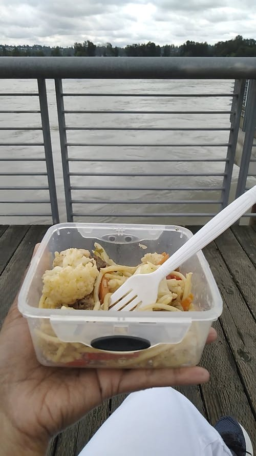 A Person Having a Meal on a Plastic Container
