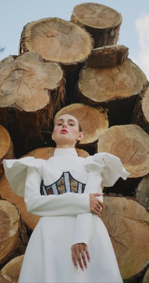 Woman Posing In Front of Logs