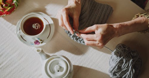 Person Knitting While Drinking Tea