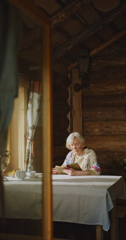 Elderly Woman Reading While Drinking Tea