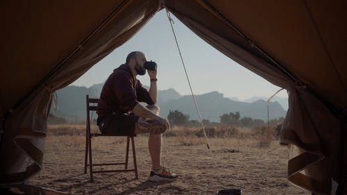 Man Drinking Outside a Tent