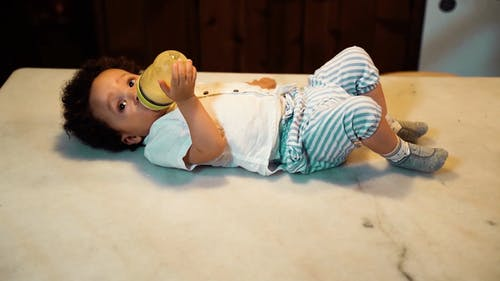 Little Boy Drinking Milk from a Baby Bottle