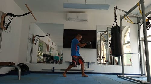 A Man Practicing His Punches Inside the Gym