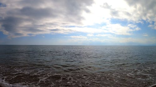 A Relaxing Scenery of Beach View Under Cloudy Sky