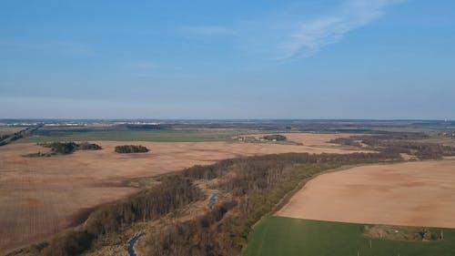 Drone Footage of Vast Agricultural Land Under Blue Sky