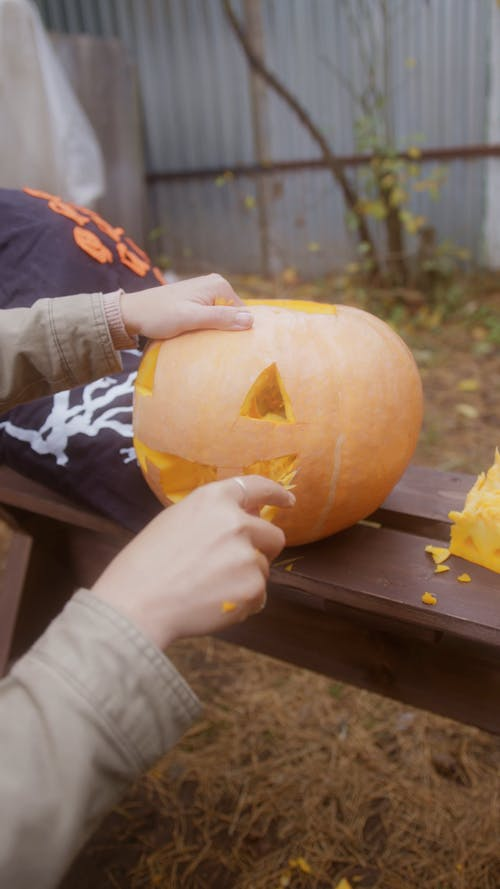 Woman Carving Pumpkin for Halloween Decoration
