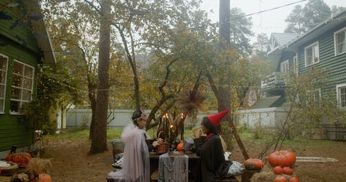 Children Wearing Halloween Costume While Sitting on the Bench