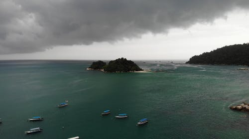 Drone Footage of Boats and Islands Under Gray Cloudy Sky