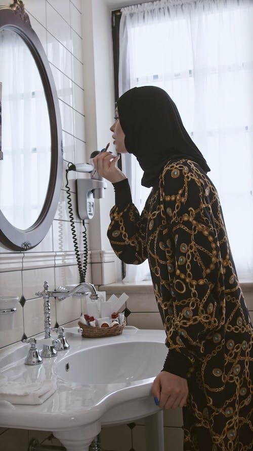 Young Muslim Woman Applying Lip Liner