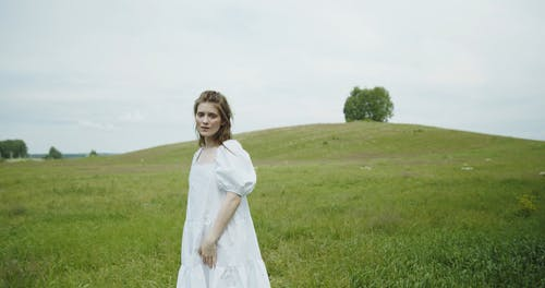 Young Woman Posing in Meadow Looking at Camera