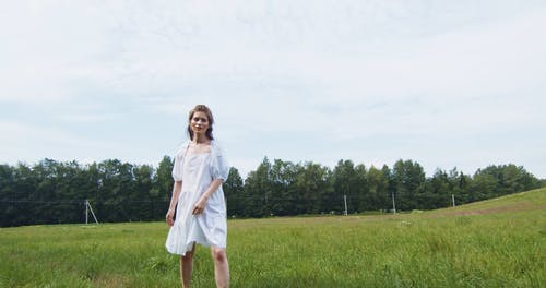 Young Woman Walking in Grass Field Looking at Camera