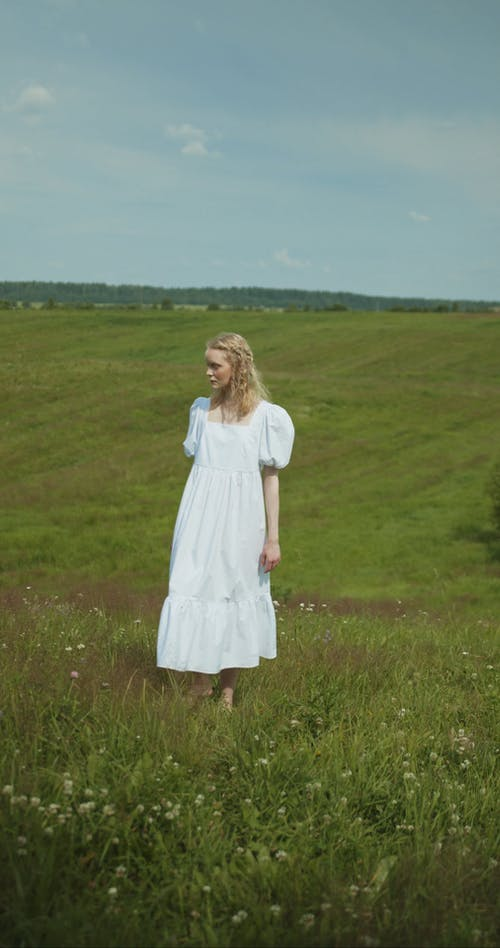 A Woman in White Dress at the Grass Fields