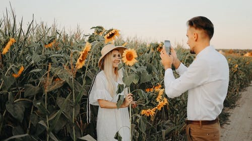 Man Taking Photo of a Woman Holding a Sunflower