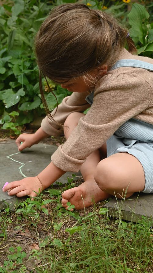 Girl Writing on a Stone with a Chalk