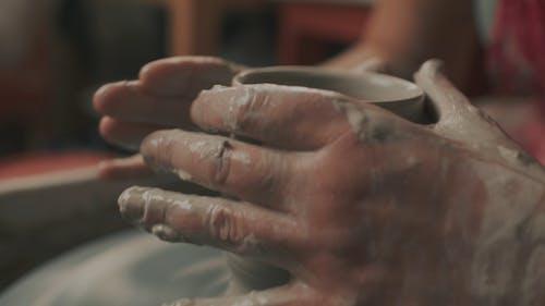 A Person Molding a Clay