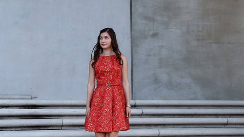 A Woman in Red Dress Walking Down the Stairs While Looking Around