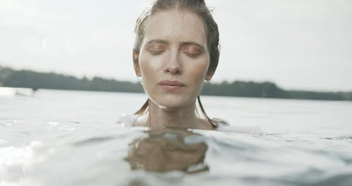 A Woman Submerging Full Body In Lake Water