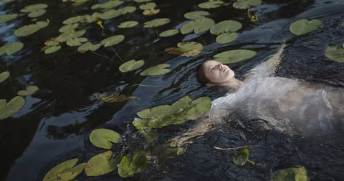 A Woman in White Dress Swimming in the Water
