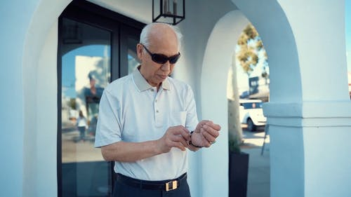 An Elderly Man Looking At Time While Waiting