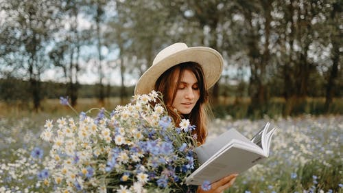 A Woman Reading A Book With Flowers On Hand