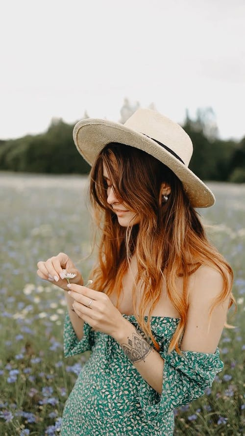A Woman In The Middle Of The Grass Flower Field