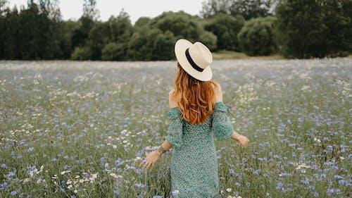 A Woman Walking In The Field Of Flowers