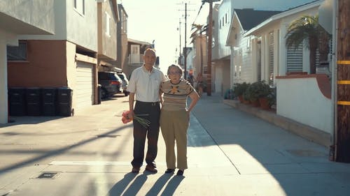 An Elderly Couple standing In The Middle Of The Street