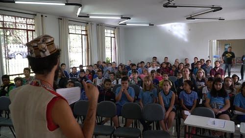 A Speaker Talking To The Crowd In A School Meeting