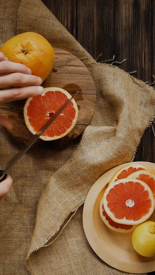 A Person Cutting a Grapefruit into Slices by Using a Knife